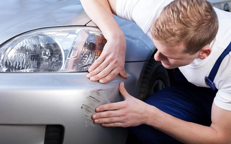 man in white t-shirt and blue overalls examining a scratched car