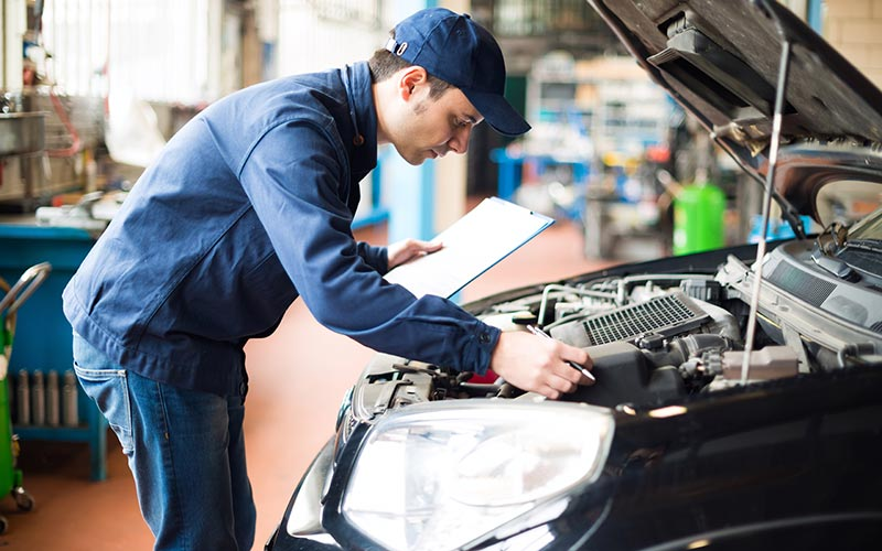 technician examining a car engine