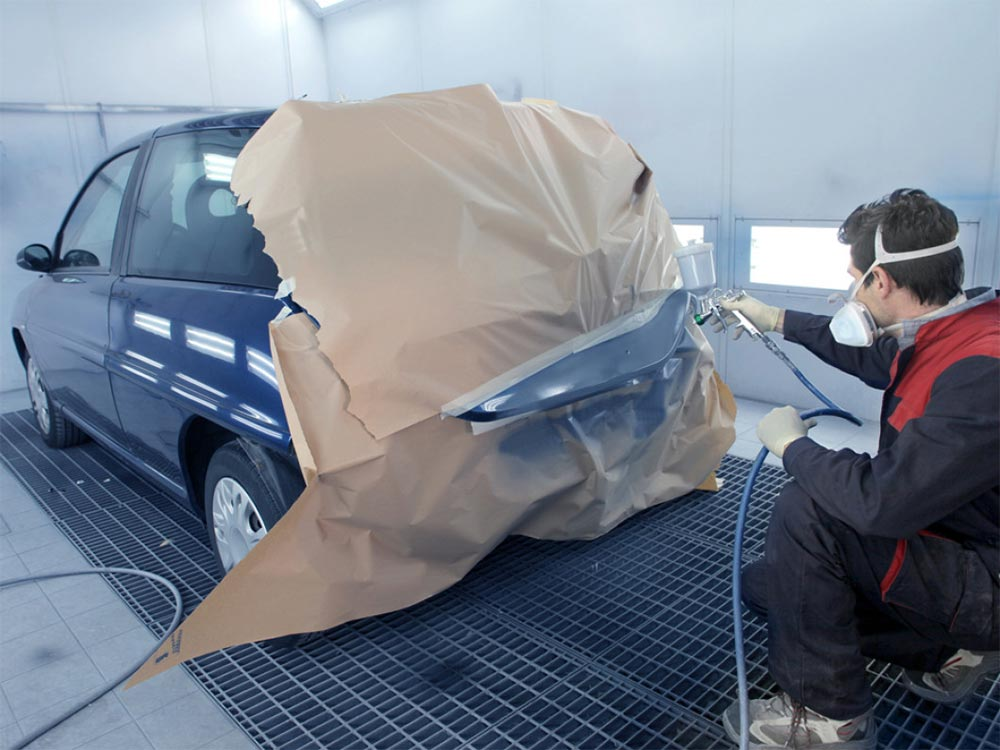 technician painting a section of a car bumper
